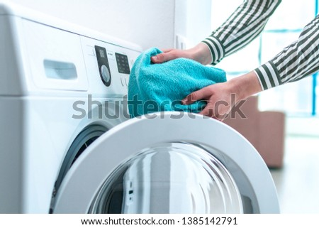 Loading towel, clothes and linen in washing machine. Doing laundry at home. Household chores and housekeeping #1385142791