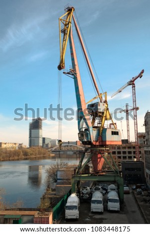 Loading-unloading crane in the river dock of an industrial enterprise. Nearby in the parking lot are three concrete mixer cars. Against the background of the blue sky and the surface of the river. #1083448175