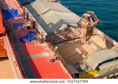 Loading wheat on cargo ship with crane and bucket. Shipment from a merchant ship to a small ship. Grapple crane fill wheat into cargo ship.