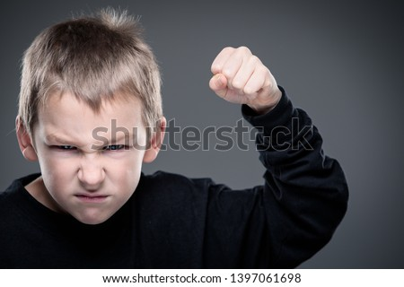 Loads of aggression in a little boy - education concept hinting behavioral problems in young children (shallow DOF) - little boy with hands clenched into fists about to punch someone #1397061698