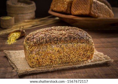 loaf bread pão de forma with sesame seeds, sunflower seeds,  linsced, oatmeal, barley, rye, chia, pumpkin seed, poppy, nutmeg, on rustic wooden table with other breads and ingredients in background