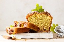 Loaf cake with polenta, grape, thyme and powdered sugar on white wooden board, light concrete background. Selective focus.