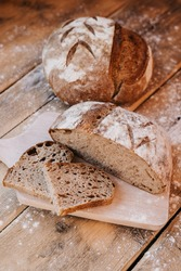 Loaf of a Home made Sourdough bread. Healthy food. Rustic wooden background.