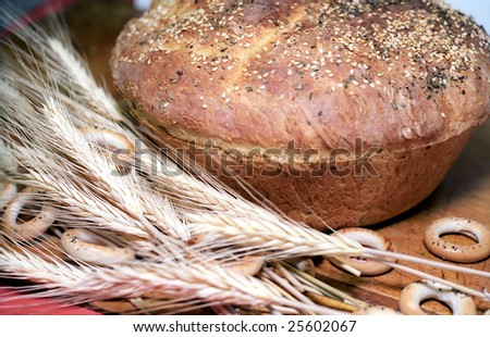 Loaf of bread with biscuits and wheat-ears close up