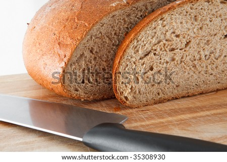 Loaf of bread with knife on wooden board