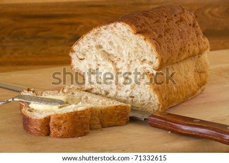Loaf of fresh baked homemade bread on cutting board with serrated knife and one slice buttered.