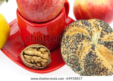 loaf with poppy seeds, quince, apples and walnuts in a cup and saucer isolated on white
