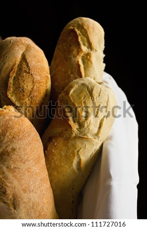 Loaves of rustic bread in a basket with a white cloth and black background