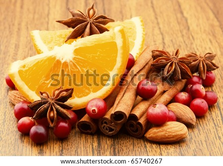 Lobes of an orange with cinnamon, an anise and a cranberry closeup
