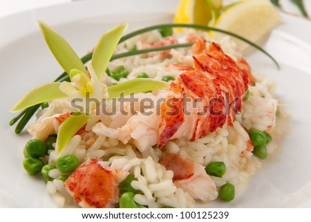 Lobster and green pea Risotto garnished with chives, lemon, and orchid flower.