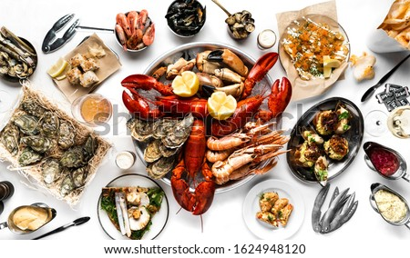 Lobster and seafood party table with oyster, crab, clams, shrimps and crayfish on white tablecloth photographed from above