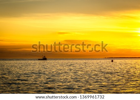 Lobster boats silhouetted against the golden sunset along the Nova Scotia coastline.