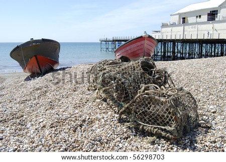 Lobster pots and fishing boats on shingle beach by the pier at Bognor Regis. West Sussex. England
