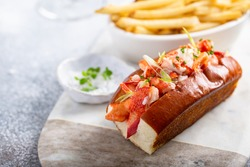 Lobster roll on a brioche bun with fries on a marble board