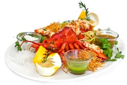 Lobster served with the vegetables on a white plate. Isolated