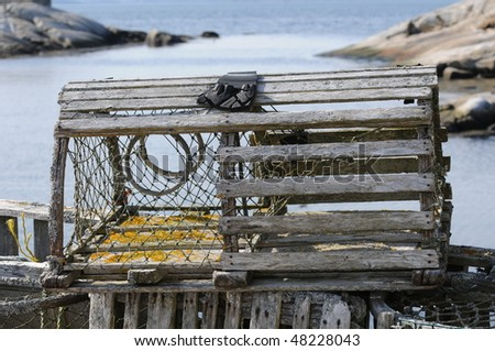 Lobster trap with Peggys Cove harbour in background