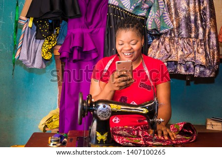 local african tailor in her workshop smiling while viewing something on her phone