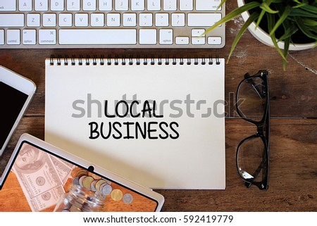 Local Business concept with smartphone, keyboard, glasses, keyboard on wooden table