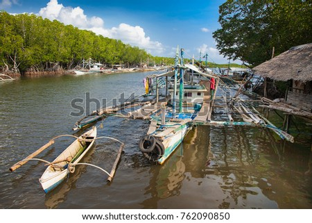 Local fisherman's boat on the river flows through mangroves forest  in northern Palawan, Philippines.