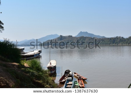 Local fishing boats sit on the still and tranquil Mekong River in Luang Prabang, Laos in mid-February, with a clear blue sky that glistens brightly in the background.