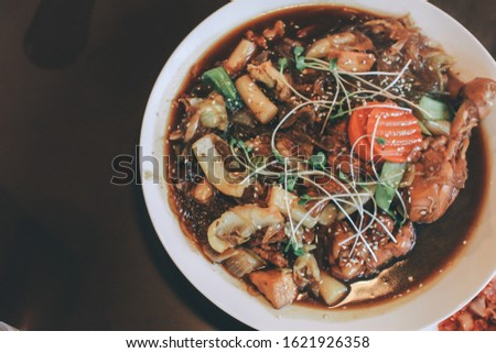 Local Korean food Braised chicken (Jim dak or Jjim Dak) made with cutted chicken, onion, sweet potato vermicelli, and other vegetables, marinated in a spicy soy sauce in metal hot pot on stove,  Stockfoto ©