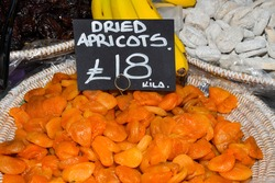 Local produce for sale displayed at the market. Borough farmer's market in London. Organic and bio fresh healthy eating concept. Dried fruits in baskets: apricots, figs, prunes, Medjool dates