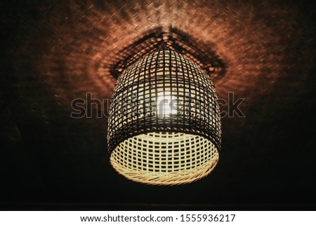 Local shaped lamps on ceiling against dark background, ceiling lamps with abstract ornament as chandelier Low-angle under lamp made of bamboo baskets with warm light hanging in darkness, which are nat #1555936217