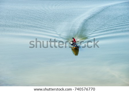 Local traditional fishing long tail boat and fisherman in lake : Ubol Ratana Dam, Khon Kaen, Thailand  #740576770