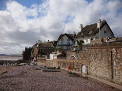 Local vintage historical cottage houses with straw roofing and high stone walls by the seaside beach in England