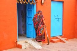 Local woman sweeping yard in Taj Ganj neighborhood of Agra, Uttar Pradesh, India. Agra is one of the most populous cities in Uttar Pradesh