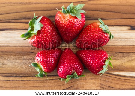 locally grown organic strawberries arranged in a circle on a wooden table