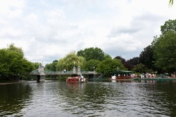 Locals and tourists enjoying a ride on the famous swan boats at the Boston Public Garden in Boston, Massachusetts, USA on a sunny summer day