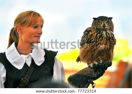 LOCARNO, SWITZERLAND - MAY 21: Lady trainer with a european eagle owl at the Lucarno Falconry  exhibition:  May 21, 2011 in Locarno Switzerland