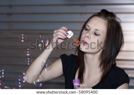 Location shoot of a beautiful young woman blowing bubbles, wearing a black top and standing in front of a garage door.