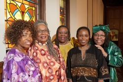 Location shot of colorfully dressed older African women dressed in colorful outfits in a church.