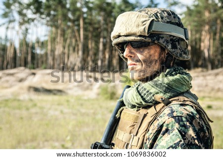Location shot of United States Marine with rifle weapons in uniforms. Military equipment, army helmet, warpaint, smoked dirty face, tactical gloves. Weapons, army, american pride, patriotism concept