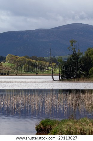 Loch Pityoulish, Speyside,Scotland, with distant mountain blue-grey under cloud, sunlight on slopes and breeze ruffling water on the surface of the loch. Taken in May.