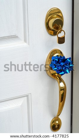 Lock and handle on door of new home with a bow on the handle - stock photo