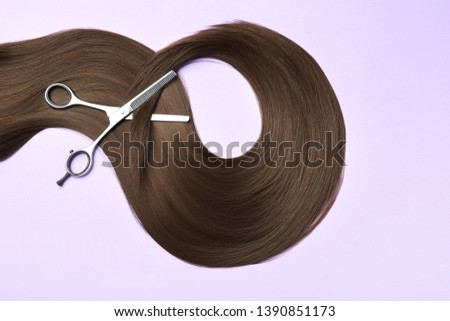 Lock of brown straight hair and thinning scissors on color background, flat lay
