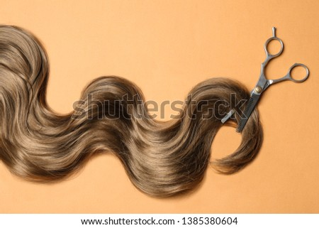 Lock of brown wavy hair and thinning scissors on color background, flat lay