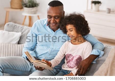 Lockdown activities. African American grandpa reading interesting book to his granddaughter at home Foto stock ©
