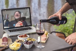 Lockdown aperitif video call party. Adult men are making a pre-meal aperitif with snacks, wine, and Italian appetizers together at home using teleconference platform apps during COVID-19 restrictions