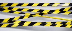 Lockdown. Do Not Cross criminal area. Yellow and black warning police strip line isolated on gray background. Caution lines. Danger and risk tape. Industrial protection sticky tape. Set small signs
