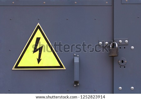 Locked electric panel with attention sign on the grey wall of transformer substation. Closed overhead lock and high voltage sign