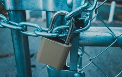 Locked Gate/Boarder Tethered by metal chain and padlock. Toned photo. Closed borders immigration concept.