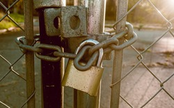Locked Gate Tethered by metal chain and old rusty padlock. Lockdown concept.