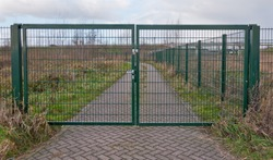 Locked green fence on an access road
