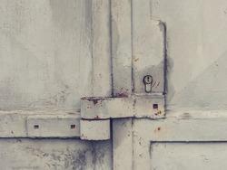 Locked industrial door. Rusty padlock hasp welded on metal sheet door and small locking insert. Cracked vintage grey brown paint.