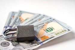 Locked lock on banknotes as a concept of financial security of deposits and money storage
