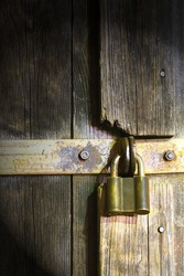 Locked rusty padlock on old wooden door